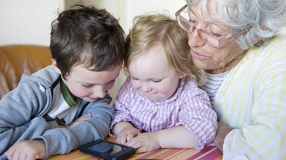 Zwei kleine Kinder schauen zusammen mir ihrer Oma auf ein Smartphone.