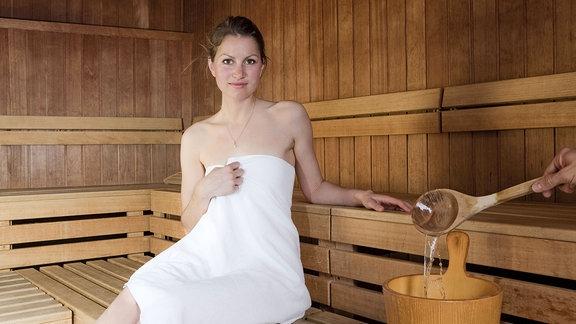 Eine Frau sitzt in einer finnischen Holzsauna.