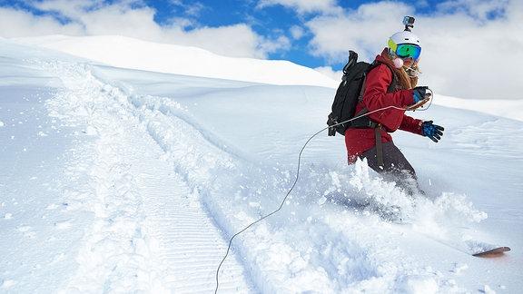 Ein Mädchen auf einem Snowboard trägt einem Helm mit einer Kamera.