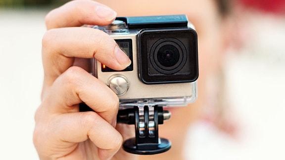 Eine Frau fotografiert mit einer Actioncamera.