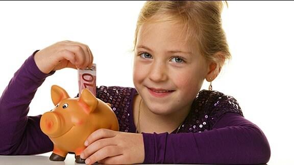 Ein Mädchen steckt einen Zehn-Euro-Schein in eine Steckdose.