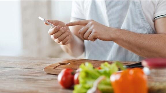 Ein Mann mit Schürze sitzt an einem Küchentisch und bedient ein Smartphone, vor Ihm auf dem Tisch liegt Gemüse