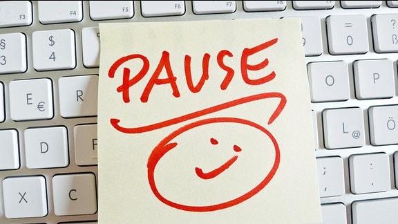 """""""Pause"""" steht auf einem Zettel, der auf einer Tastatur liegt"""