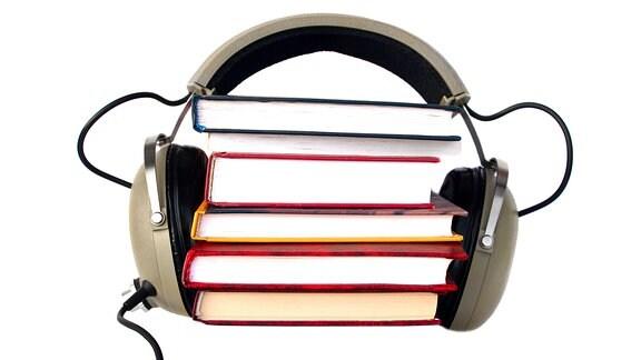 Ein Kopfhörer ist um einen Stapel Bücher geklemmt.