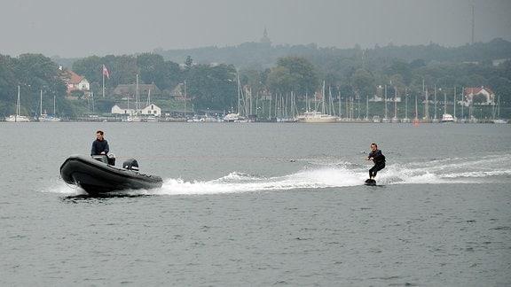 Ein Mann fährt Wasserski und wird von einem Schlauchboot mit Außenbordmotor gezogen