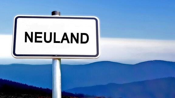 """Ein Straßenschild mit der Aufschrift """"Neuland"""" vor einem bergigen Hintergrund"""