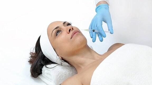 Illustration - Einem Model wird eine Botoxspritze vor die Lippen gehalten.