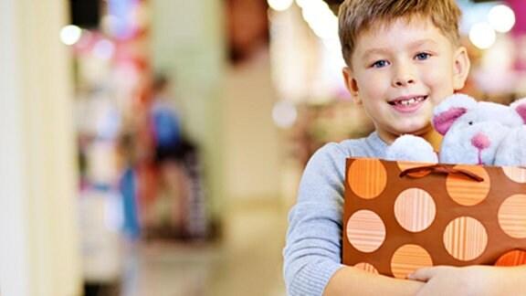 Ein Junge hält stolz eine Einkaufstüte mit einem Teddybären darin.