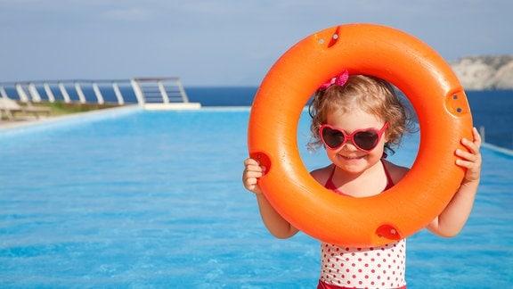 Kleines Mädchen am Pool schaut durch Rettungsring
