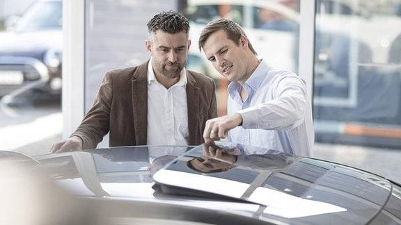 Autoverkäufer spricht mit einem Kunden