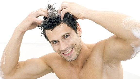 Junger Mann wäscht sich die Haare in einer Badewanne