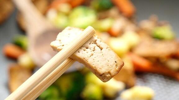 Zwischen zwei Essstäbchen steckt ein Stück Tofu