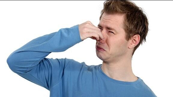Ein Mann hält sich die Nase zu.