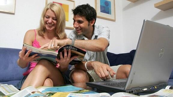 Frau und Mann mit Reiseprospekten und Laptop zu Hause auf dem Sofa.