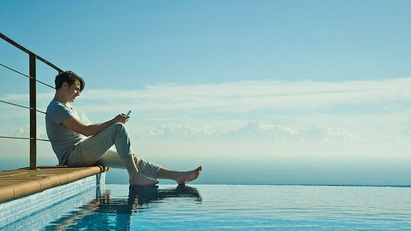 Ein Mann sitzt mit einem Mobiltelefon an einem Pool