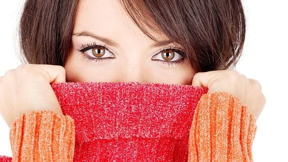 Eine junge Frau hat sich den Kragen ihres Rollkragenpullovers bis über die Nase gezogen