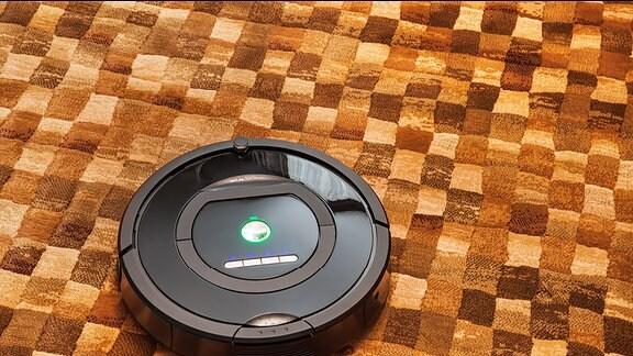 Ein runder Staubsaug-Roboter auf einem braunkarierten Teppich.
