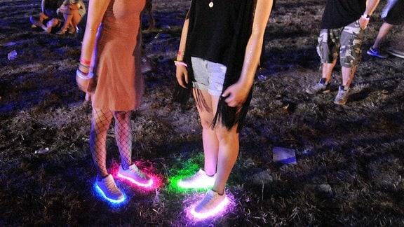 Zwei Festivalbesucher tragen LED - Schuhe, die permanent die Farben wechseln.