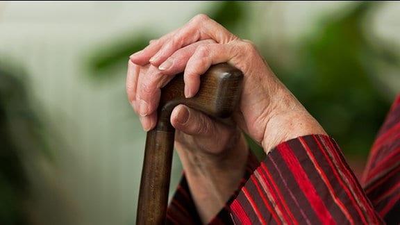 Die Hände einer alten Frau umfassen den Griff eines Gehstocks.