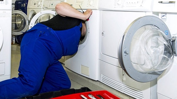 Ein Techniker repariert eine Waschmaschine.