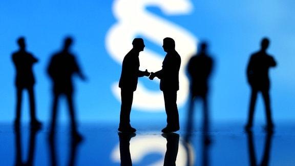 Manager Figuren in Anzuegen stehen vor einem Paragrafen Zeichen und geben sich die Hand.