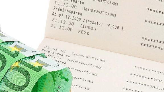 Sparstrumpf mit Geld neben Kontoauszügen.