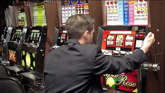 Ein Mann spielt an einem Spielautomat