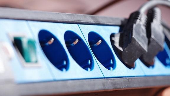 zwei schwarze Stecker in einer Steckdosenleiste
