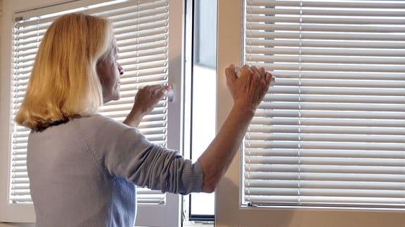 Frau öffnet Fenster.