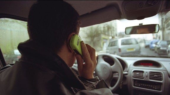 Mann telefoniert im Auto mit altmodischem Mobiltelefon (Symbolbild)