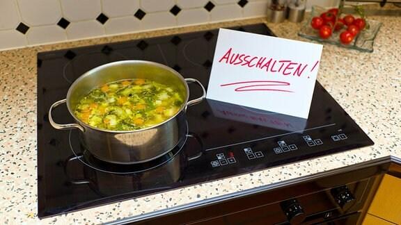 """Auf einem Glaskeramikkochfeld steht ein Topf mit Suppe und daneben ein hangeschriebenes Schild mti der Aufschrift """"Ausschalten"""""""