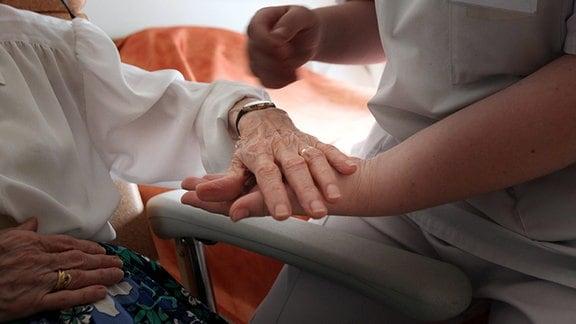 Eine Pflegerin nimmt die Hand einer alten Frau, die in einem Stuhl sitzt.