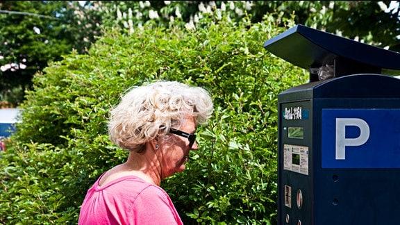 Seniorin mit Sonnenbrille vor einem Parkscheinautomaten