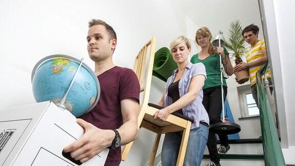 Freunde helfen bei einem Umzug und tragen Kisten, Pflanzen und Möbel durch ein Treppenhaus