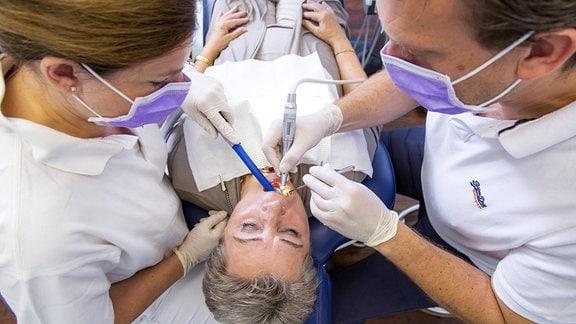 Ein Zahnarzt behandelt mit einer Zahnarzthelferin eine Frau.