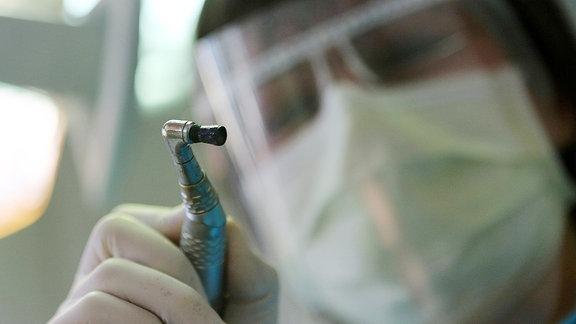 Ein Zahnarzt mit Schutzvisier beugt sich über einen Patienten.