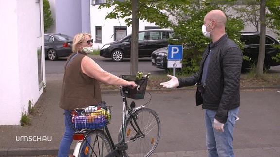 Eine Frau und ein Mann unterhalten sich auf der Straße.