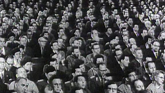 Menschen sitzen im Publikum.