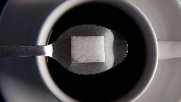 Draufsicht auf ein Stück Würfelzucker, das auf einem Teelöffel liegt, der sich über einer Tasse Kaffee befindet.