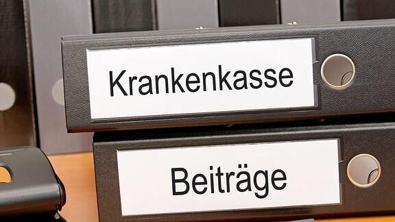 Zwei Ringordner mit der Aufschrift Krankenkasse bzw. Beiträge.