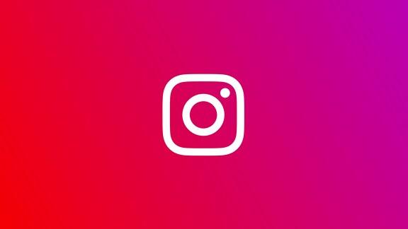 Das weiße Logo von Instagram auf einem pinken Hintergrund. Das Logo besteht aus einem weißen Quadrat mit runden Ecken und einem Kreis in der Mitte. Es steht symbolisch für eine Kamera.