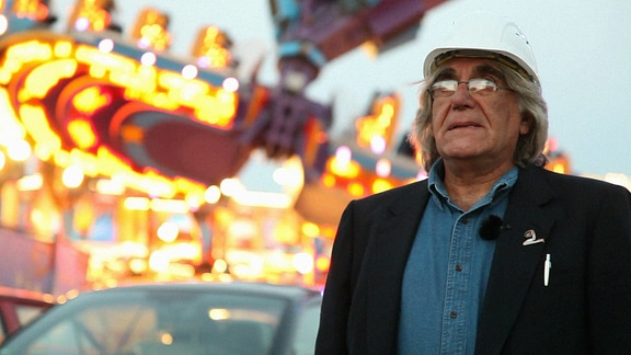 Ein Mann mit Brille und Baustellenschutzhelm, in Jacket und Jeanshemd gekleidet, steht vor einem erleuchteten Fahrgeschäft und blickt auf einen unbestimmten Punkt in der Ferne.