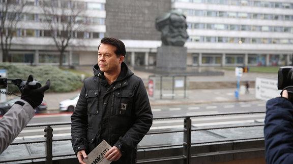 Ein Mann schaut während Dreharbeiten in die Kamera.