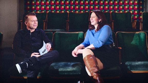 Moderator Markus Kavka sitzt mit Annegret Richter in einer Reihe von Kinositzen. Sie unterhalten sich.