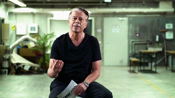 Der Moderator Markus Kavka sitzt auf einem Hocker in der Mitte eines Raumes und spricht in die Kamera.