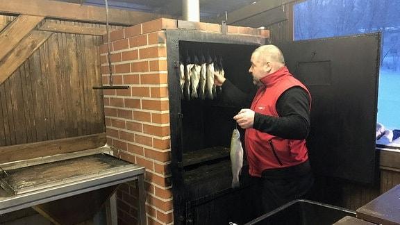 Ein Mann hängt Fisch in einen Räucherofen.