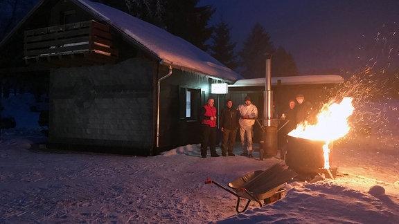 Mehrere Männer stehen vor einer Hütte. Vor ihnen steht eine Tonne in der ein Feuer brennt, Flammen schlagen herraus.