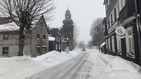 Straße im Dorf mit Schneebergen am Straßenrand.