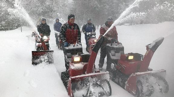 Mehrere Männer mit Schneefräsen auf einem verschneiten Weg.