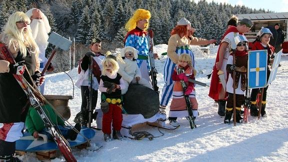 Verkleidete Kinder und Erwachsene mit Skiern und Schlitten stehen auf einem verschneiten Berg